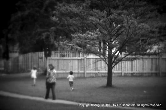 mother and two children walking on and along the sidewalk