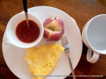 plate containing cup of salsa, 2-egg omelet; sup of water and utensils